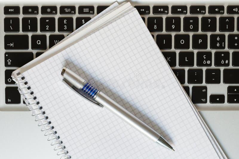 Ordinateur portable avec le bloc-notes, le stylo et le clavier image stock