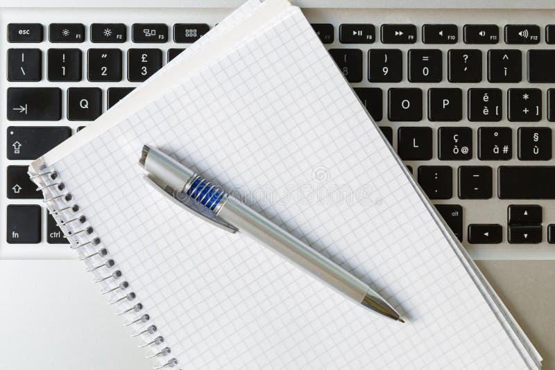 Ordinateur portable avec le bloc-notes, le stylo et le clavier photographie stock libre de droits