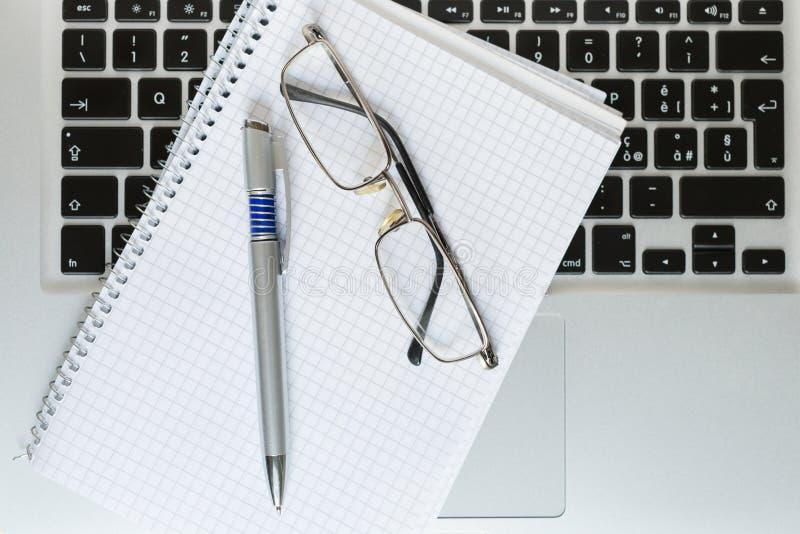 Ordinateur portable avec le bloc-notes, le stylo, les verres et le clavier image libre de droits