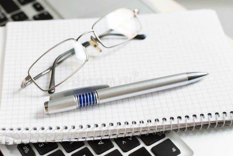 Ordinateur portable avec le bloc-notes, le stylo, les verres et le clavier image stock