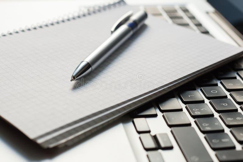 Ordinateur portable avec le bloc-notes, stylo sur la table ene ivoire image libre de droits