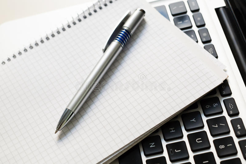 Ordinateur portable avec le bloc-notes, stylo sur la table ene ivoire photos stock