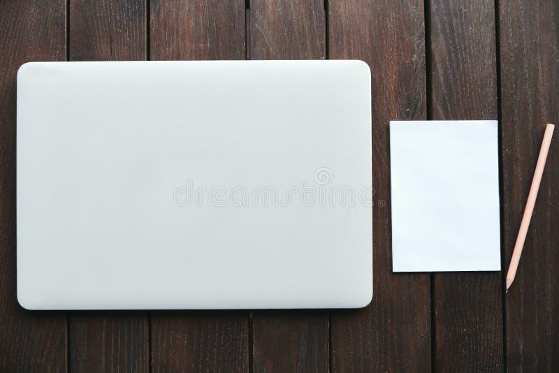Ordinateur portable avec le carnet et le crayon sur la table en bois photo stock