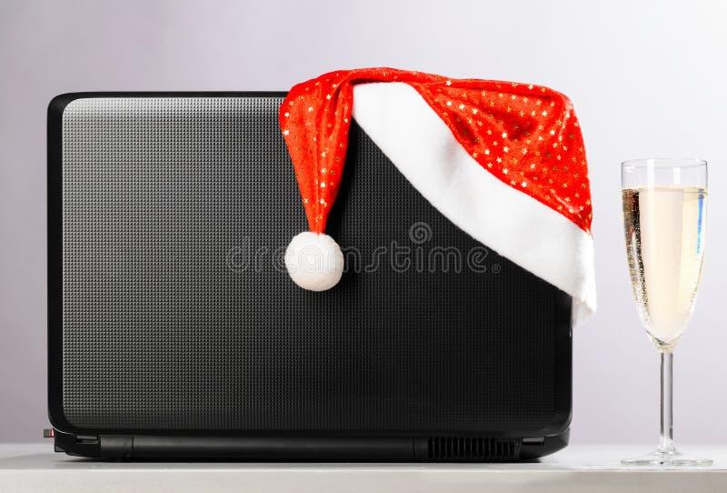 Ordinateur portable avec le chapeau et le vin de Santa photos stock