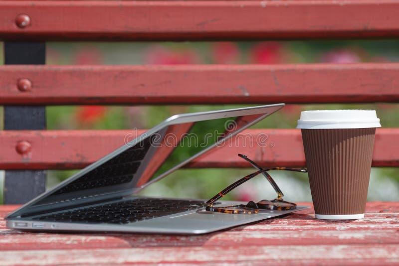 Ordinateur portable avec les verres et le carnet se trouvant sur le banc en parc de ville, étude extérieure ou concept fonctionna photo libre de droits