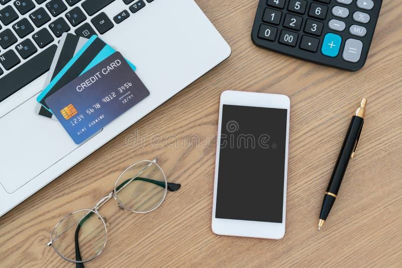 Ordinateur portable, cartes de crédit, calculateur, stylo pour notbook et lunettes sur le bureau, concept de compte et d'épargne photo libre de droits
