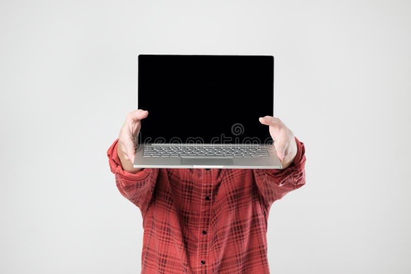Ordinateur portable d'homme et écran de transport de représentation de lui se tenant cachant son visage photos libres de droits