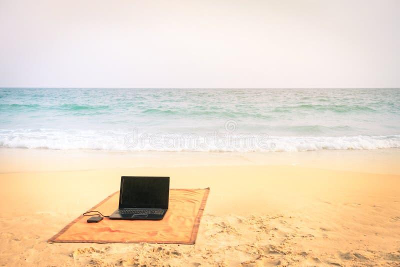 Ordinateur portable d'ordinateur à la plage sur la destination tropicale photo stock