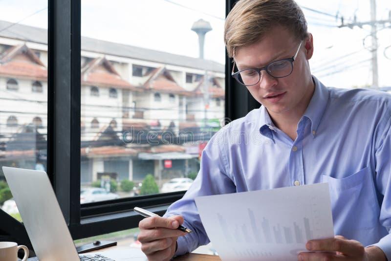 Ordinateur portable d'utilisation d'homme d'affaires avec le document de plan d'action sur le lieu de travail photos libres de droits