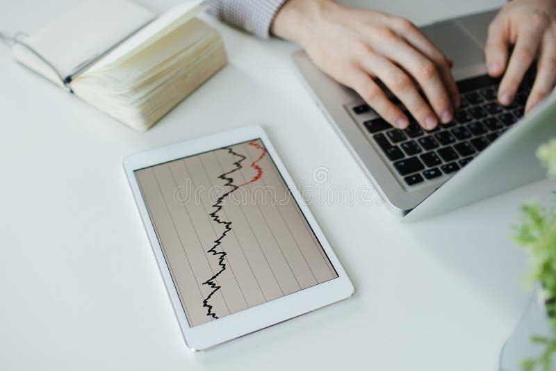 Ordinateur portable de dactylographie d'homme d'affaires déprimé avec le mauvais diagramme de marché boursier photos stock