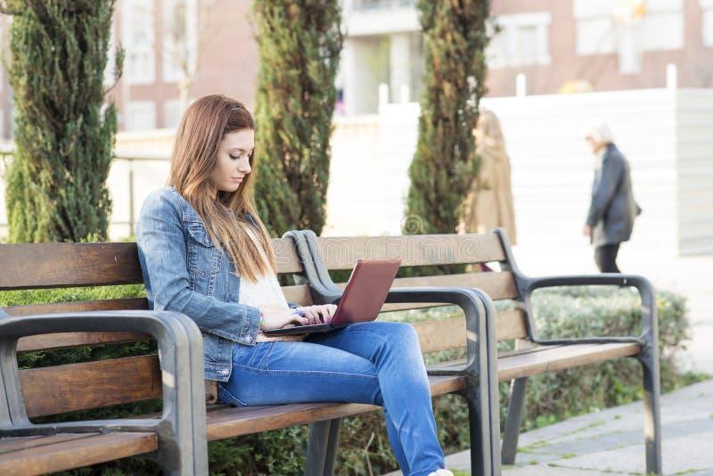 Ordinateur portable de jeune femme en parc. photo libre de droits