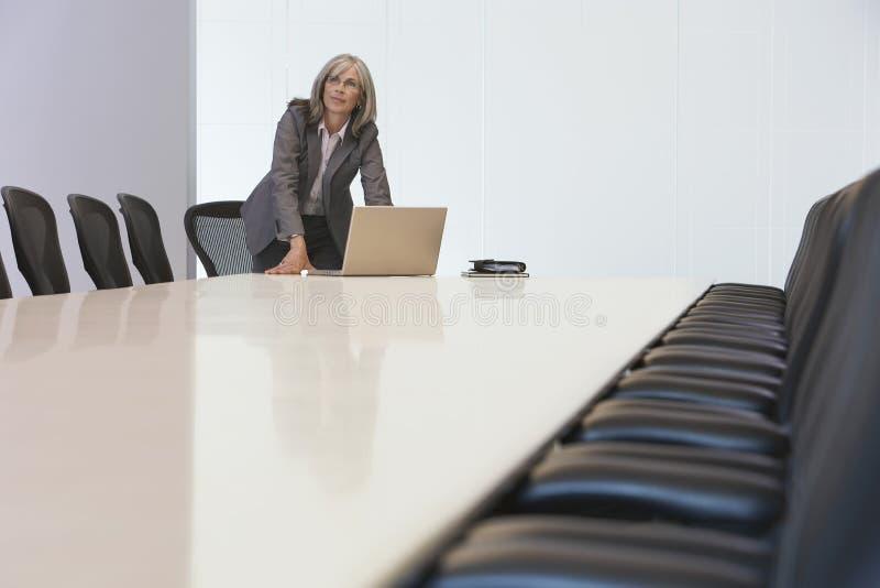 Ordinateur portable de Looking Up By de femme d'affaires dans la salle du conseil d'administration images libres de droits