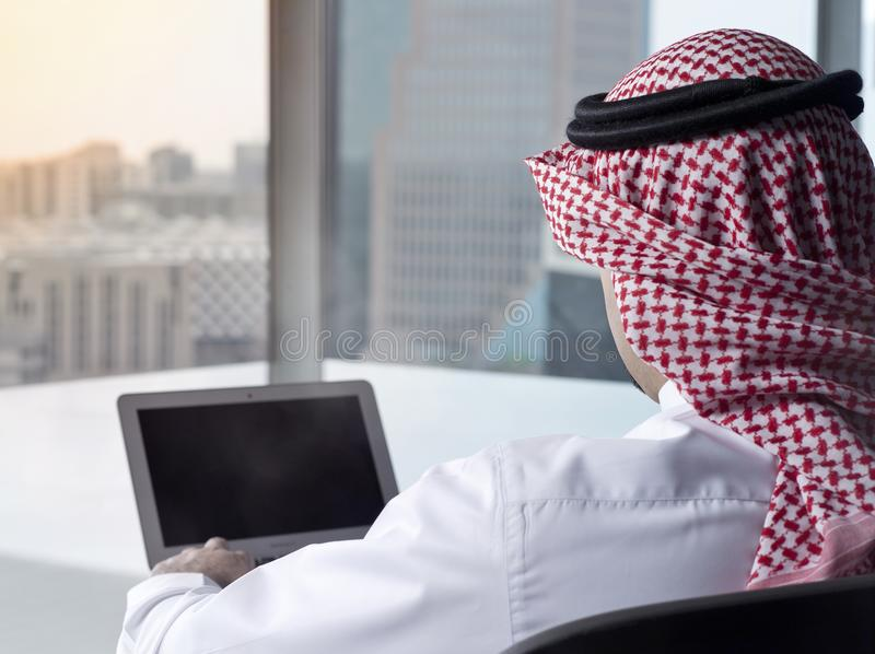 Ordinateur portable de observation d'homme saoudien à la perspective de travail photographie stock