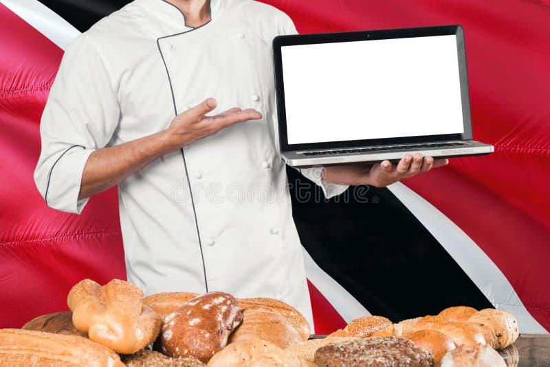 Ordinateur portable de participation de Baker sur le drapeau de Trinidad And Tobago et le fond de pains Uniforme de port de chef  photos libres de droits