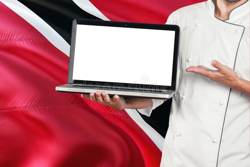 Ordinateur portable de participation de chef avec l'écran vide sur le fond de drapeau de Trinidad And Tobago Faites cuire l'unifo photos stock
