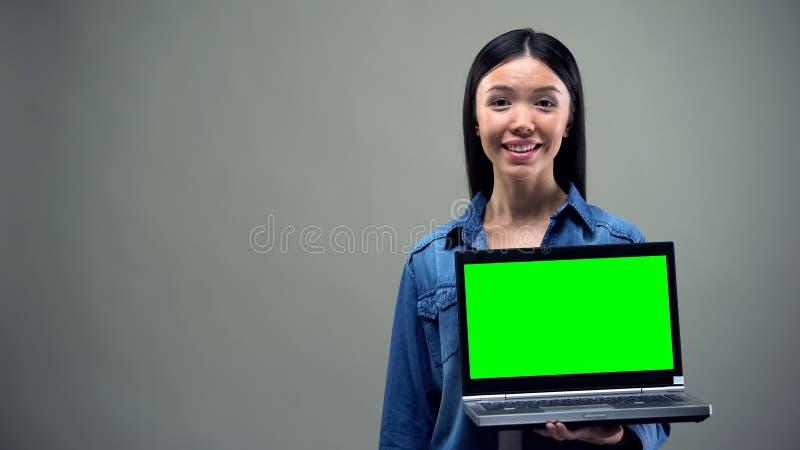 Ordinateur portable de participation de fille avec l'?cran vert, fou au sujet des remises, faisant des emplettes en ligne images stock