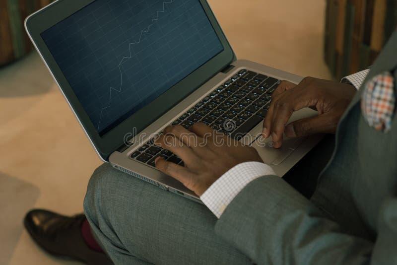 Ordinateur portable de port de participation de costume d'homme d'affaires sur son recouvrement et examination encaisser des diag photographie stock libre de droits