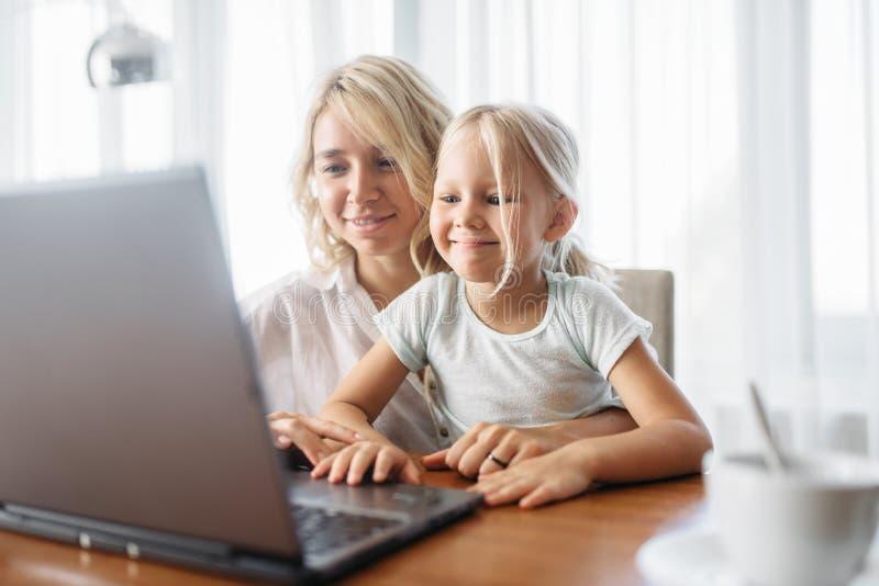 Ordinateur portable de sourire d'utilisations de mère et d'enfant à la maison photo libre de droits