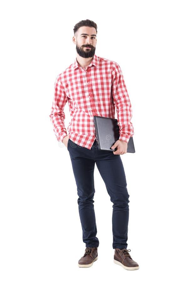 Ordinateur portable de transport de sourire satisfaisant de jeune homme d'affaires sous le bras regardant l'appareil-photo photos stock