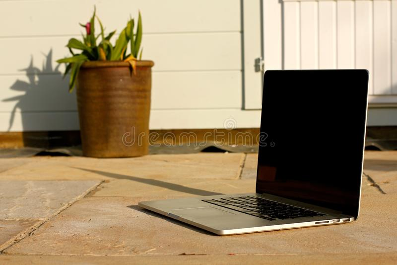 Ordinateur portable dehors sur le patio photographie stock libre de droits