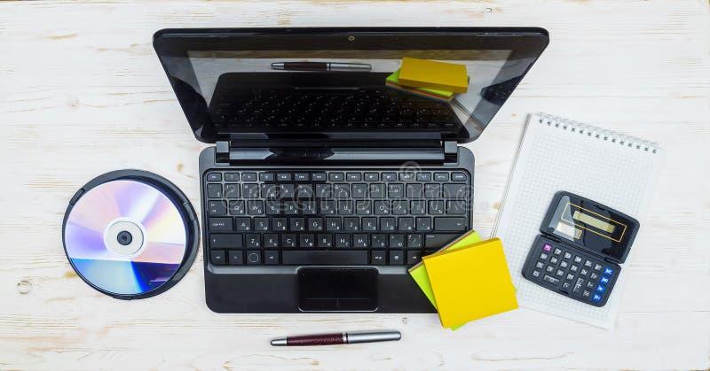 Ordinateur portable, disques lasers, une calculatrice de bloc-notes et un stylo-plume dessus photographie stock