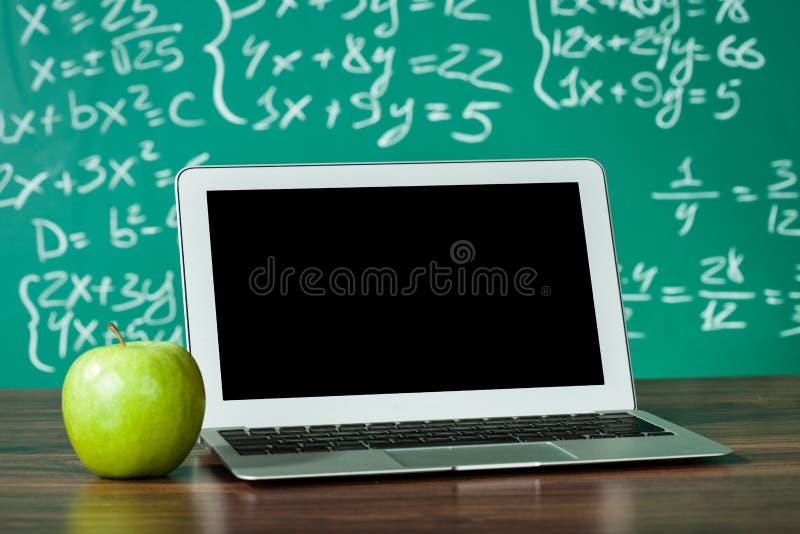 Ordinateur portable et pomme sur le bureau images stock