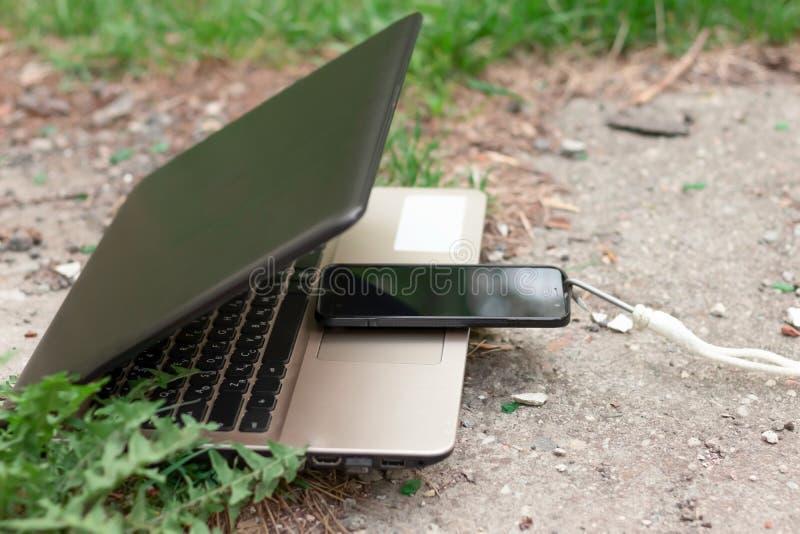 Ordinateur portable et smartphone pendant le d?jeuner Le dispositif puissant absorbe l'instrument p?rim? Abstraction photo libre de droits