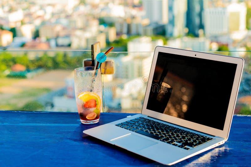 Ordinateur portable et verre de cocktail d'été sur une table en bois, sur un beau fond panoramique lumineux de la ville photo libre de droits