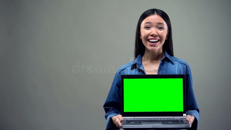 Ordinateur portable extr?mement heureux de participation de femme avec l'?cran vert, grands gains en ligne photographie stock