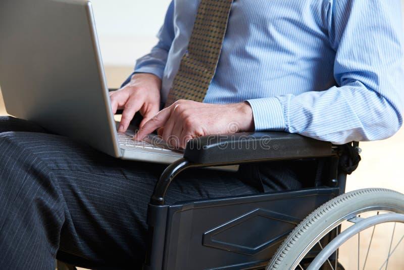 Ordinateur portable handicapé d'In Wheelchair Using d'homme d'affaires photos stock