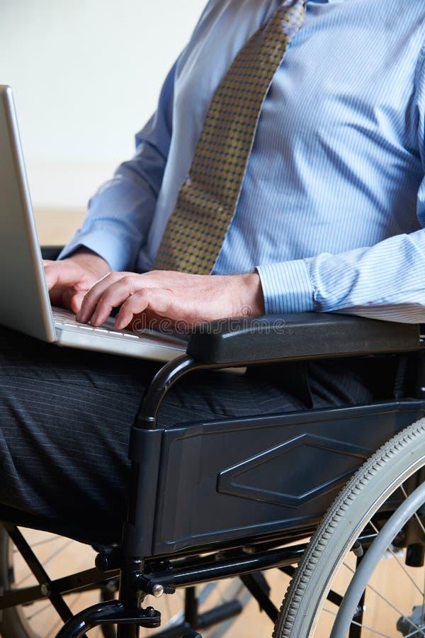 Ordinateur portable handicapé d'In Wheelchair Using d'homme d'affaires photographie stock
