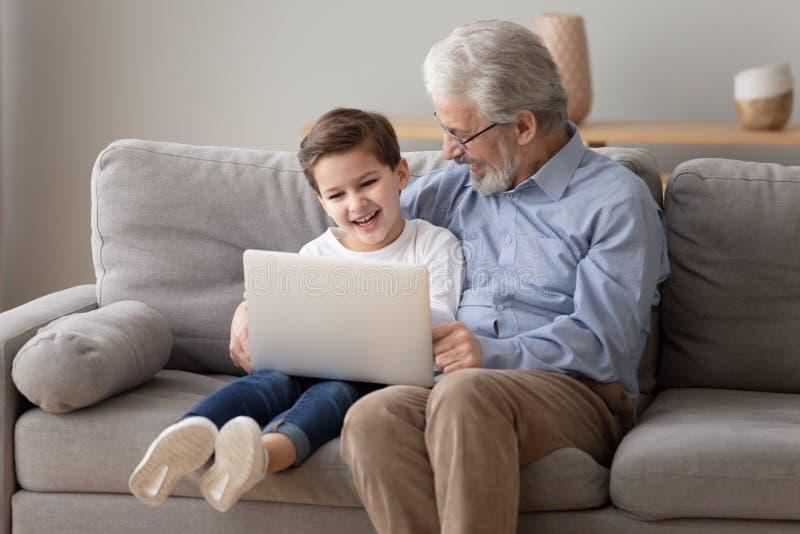 Ordinateur portable heureux de jeu de grand-p?re et de petit-fils ensemble photographie stock libre de droits