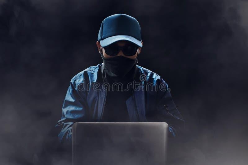 Ordinateur portable inconnu d'utilisation de pirate informatique dans la chambre noire images libres de droits