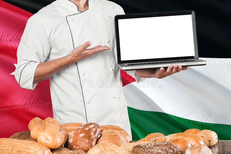 Ordinateur portable jordanien de participation de Baker sur le drapeau de la Jordanie et le fond de pains Uniforme de port de che photo stock