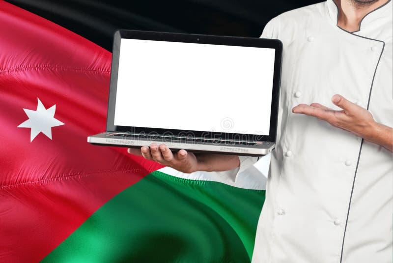 Ordinateur portable jordanien de participation de chef avec l'écran vide sur le fond de drapeau de la Jordanie Faites cuire l'uni photos libres de droits