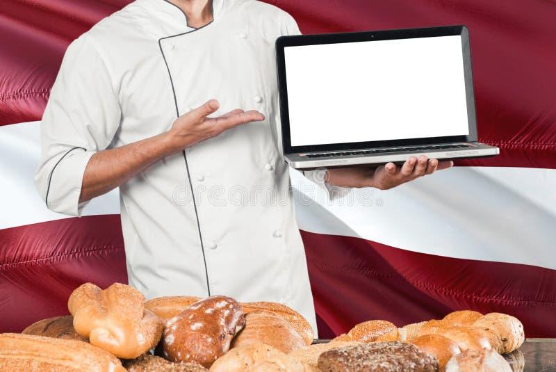Ordinateur portable letton de participation de Baker sur le drapeau de la Lettonie et le fond de pains Uniforme de port de chef d photographie stock