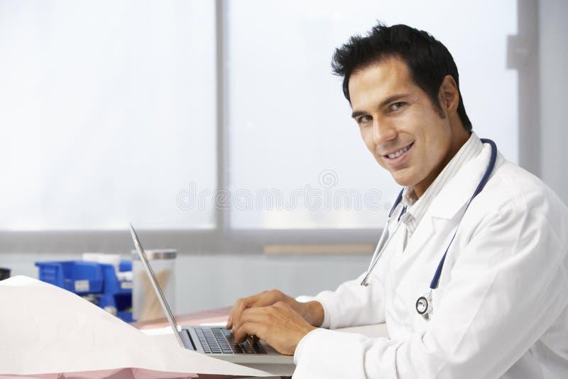 Ordinateur portable masculin de docteur In Surgery Using images libres de droits