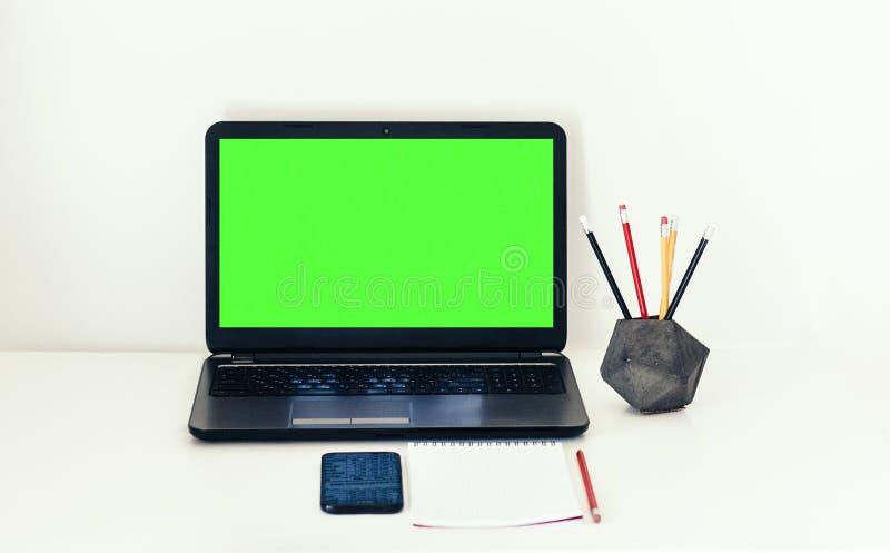 Ordinateur portable, smartphone, carnet et crayons verts d'écran dans le support concret sur la table blanche, fond de concept de images stock