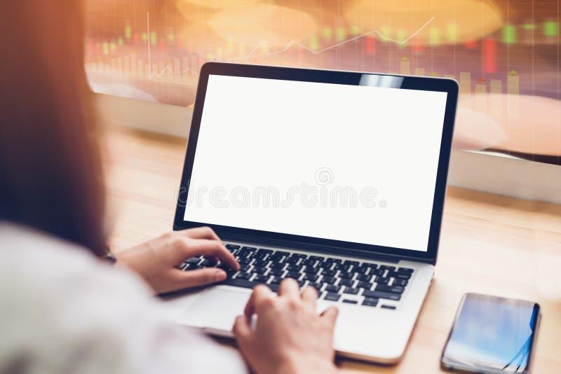 Ordinateur portable sur la table dans la chambre de bureau sur le graphique de commerce de bourse des valeurs pour le fond, pour  images stock