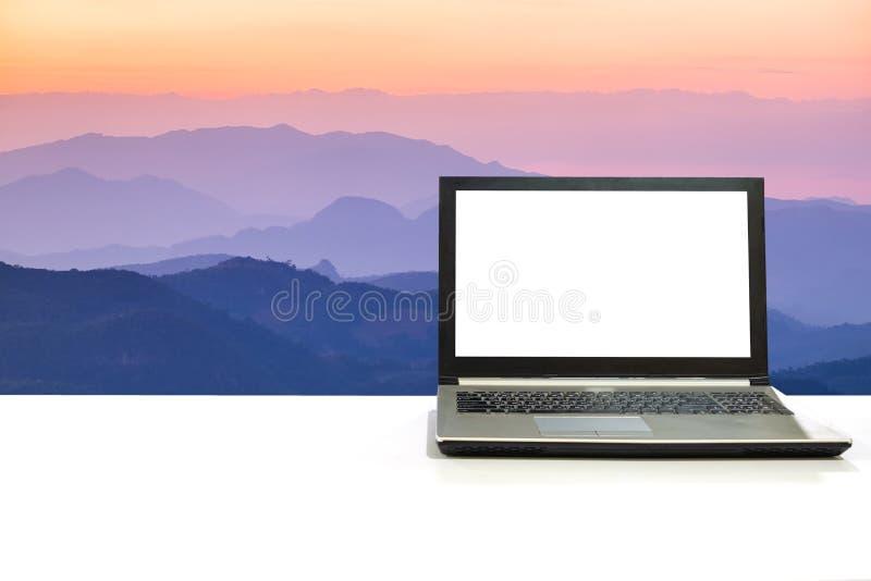 Ordinateur portable sur le bureau blanc avec le laye multicolore de montagne de scène naturelle images libres de droits