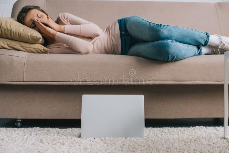 ordinateur portable sur le tapis et la jeune femme photos stock