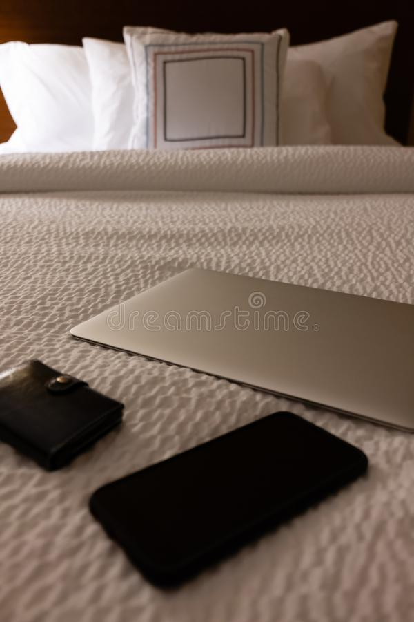 Ordinateur portable, téléphone et portefeuille sur le lit d'hôtel image libre de droits