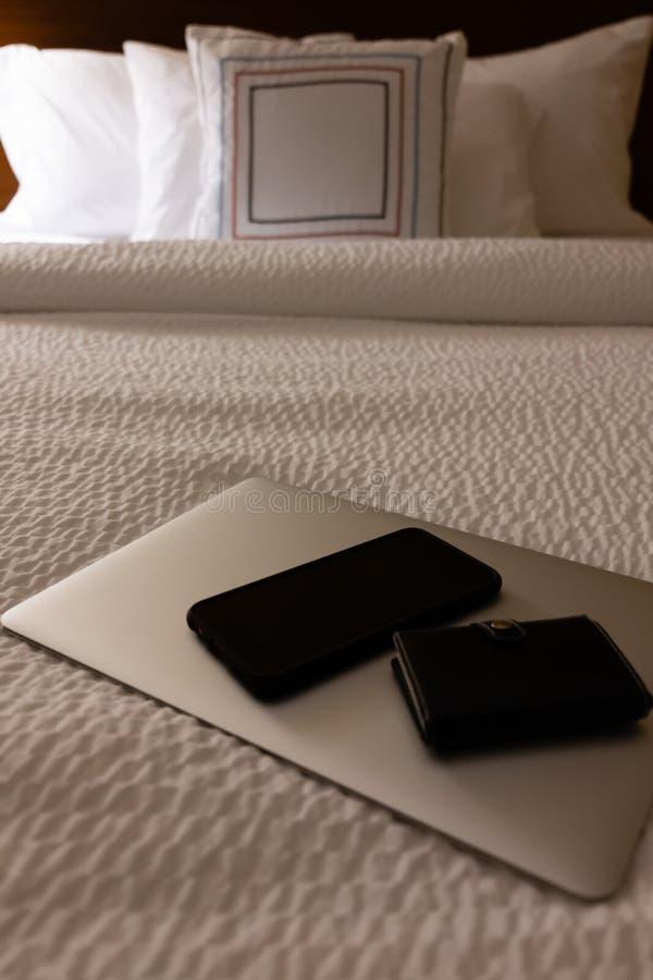 Ordinateur portable, téléphone et portefeuille sur le lit d'hôtel photographie stock libre de droits