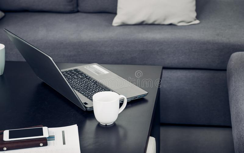Ordinateur portable, tasse de café, téléphone portable, organisateur, graphique de gestion sur le bureau au sofa dans le bureau,  photos stock