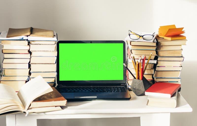 Ordinateur portable vert d'?cran, pile de livres, carnet et crayons sur la table blanche, fond de concept de bureau d'?ducation photo stock