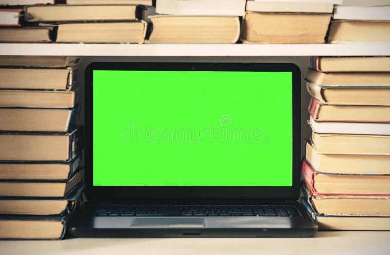 Ordinateur portable vert d'?cran, pile de livres, carnet et crayons sur la table blanche, fond de concept de bureau d'?ducation photo libre de droits