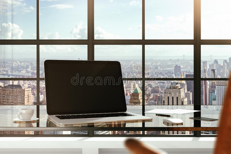 Ordinateur portable vide sur une table en verre dans des vues d'un bureau moderne et de ville photo stock