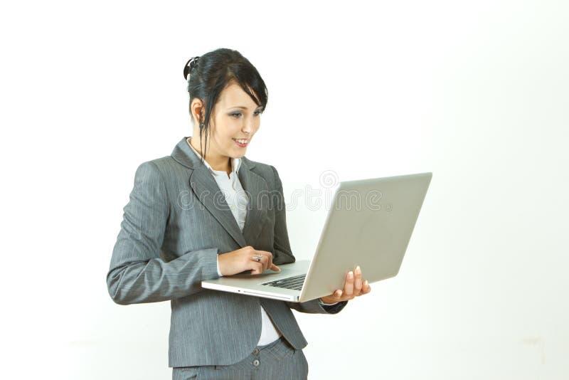 Ordinateur portatif debout de sourire de fixation de femme d'affaires photo stock