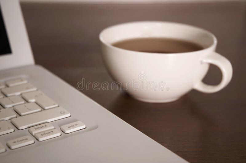 Ordinateur portatif et cuvette de thé photos stock