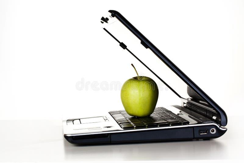 Ordinateur portatif et pomme verte photographie stock